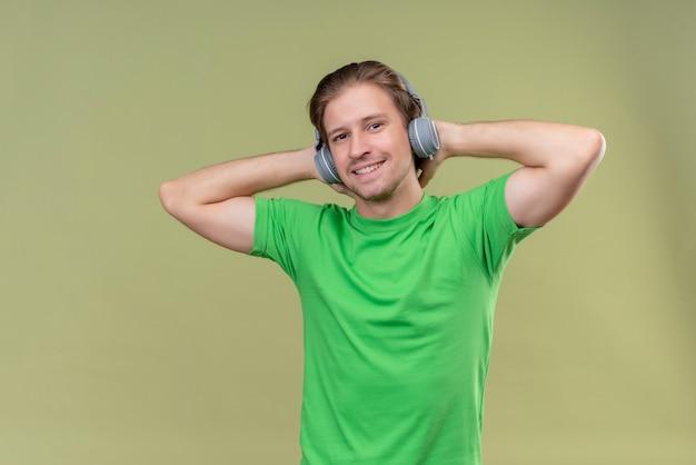Junger hübscher mann, der grünes t-shirt mit kopfhörern genießt, die lieblingsmusik genießen, die über grüner wand steht
