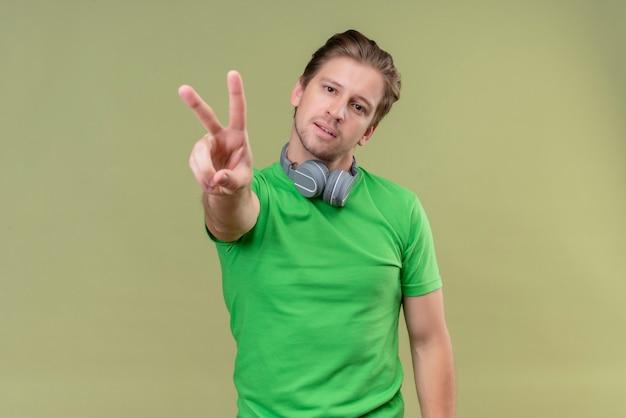 Junger hübscher mann, der grünes t-shirt mit lächelnden kopfhörern trägt und mit den fingern nummer zwei oder siegeszeichen über grüner wand zeigend zeigt