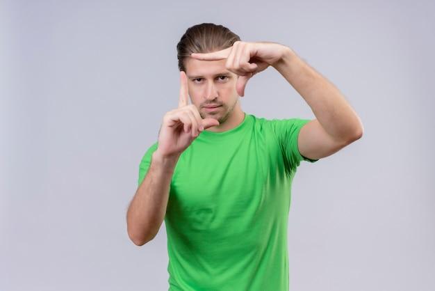 Junger hübscher mann, der grünes t-shirt trägt, das durch einen rahmen schaut, der durch seine hände gebildet wird