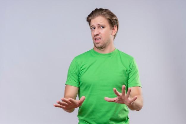 Junger hübscher mann, der grünes t-shirt trägt, das seine hände hochhält und erzählt, kommt nicht mit angewidertem ausdruck näher, der über weißer wand steht