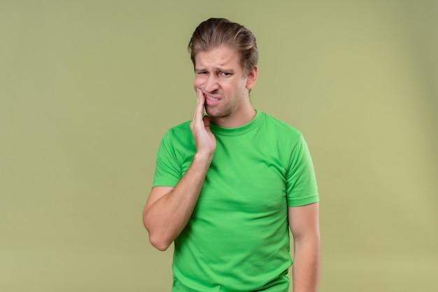 Junger hübscher mann, der grünes t-shirt trägt, das unwohl schaut, das seine wange berührt, die zahnschmerzen hat, die über grüner wand stehen