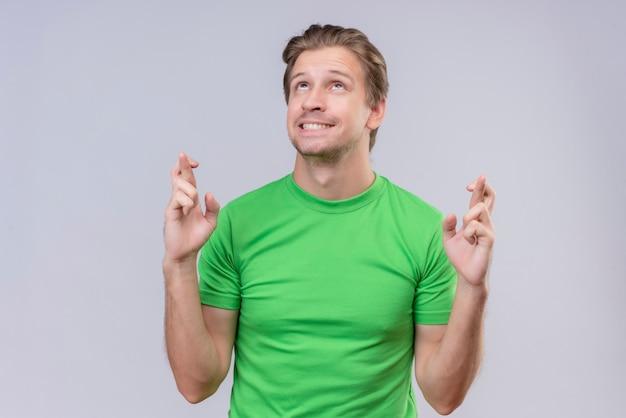 Junger hübscher mann, der grünes t-shirt trägt, das wünschenswerten wunsch kreuzt, hand mit hoffnungsvollem ausdruck kreuzend