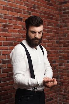 Junger hübscher mann, der hemd auf backsteinmauer korrigiert.