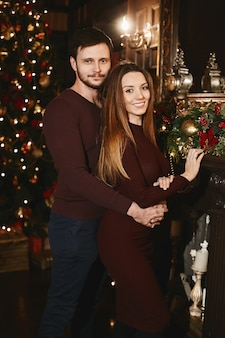 Junger hübscher mann, der herrliche junge frau im innenraum umarmt, der für weihnachten verziert wird