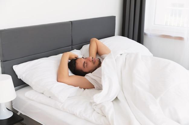 Junger hübscher mann, der in seinem bett schläft