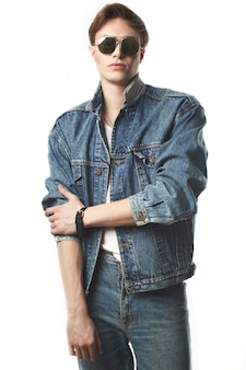 Junger hübscher mann, der jeansjaket im studio trägt