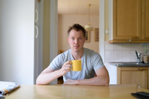 Junger hübscher mann, der kaffee durch das fenster sitzt und trinkt