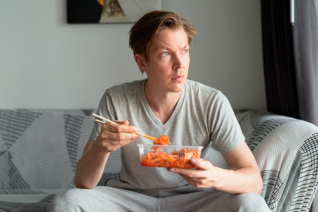 Junger hübscher mann, der kimchi isst und im wohnzimmer zu hause denkt