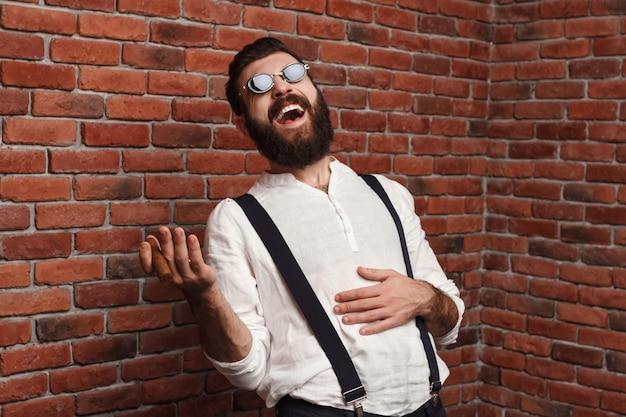 Junger hübscher mann, der lachend zigarre auf ziegelmauer lacht.