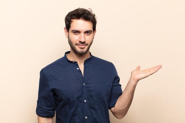 Junger hübscher mann, der lächelt, sich sicher, erfolgreich und glücklich fühlt und konzept oder idee auf kopienraum auf der seite zeigt