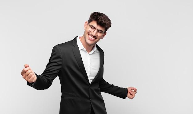 Junger hübscher mann, der lächelt, sich sorglos, entspannt und glücklich fühlt, tanzt und musik hört, spaß auf einer party hat