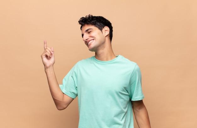 Junger hübscher mann, der lächelt, sich sorglos, entspannt und glücklich fühlt, tanzt und musik hört und spaß auf einer party hat