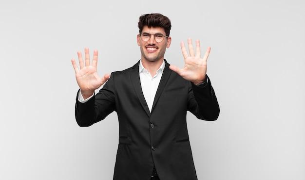 Junger hübscher mann, der lächelt und freundlich schaut, nummer zehn oder zehntel mit der hand vorwärts zeigend, herunterzählend
