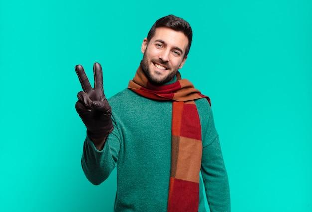 Junger hübscher mann, der lächelt und glücklich, sorglos und positiv schaut, sieg oder frieden mit einer hand gestikulierend.