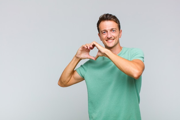 Junger hübscher mann, der lächelt und sich glücklich, süß, romantisch und verliebt fühlt und herzform mit beiden händen bildet