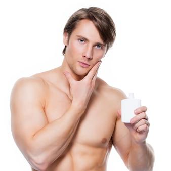 Junger hübscher mann, der lotion auf gesicht aufträgt - lokalisiert auf weiß.