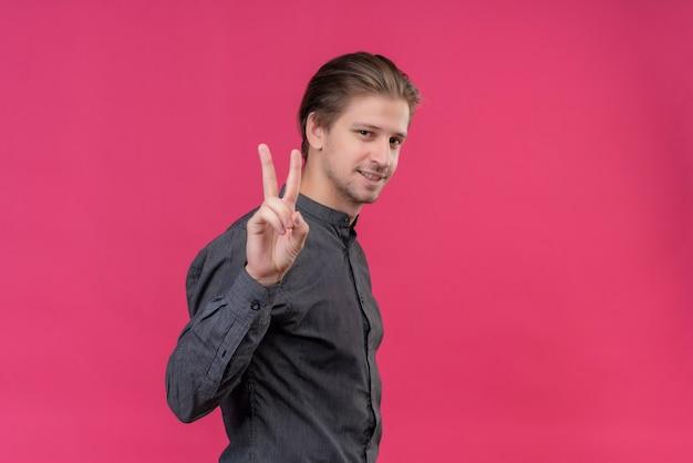 Junger hübscher mann, der mit den fingern nummer zwei zeigt und zeigt