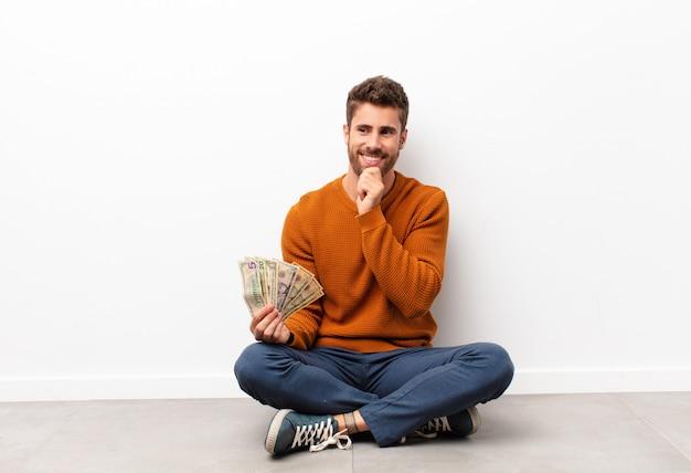 Junger hübscher mann, der mit einem glücklichen, selbstbewussten ausdruck mit der hand am kinn lächelt, sich wundert und zur seite schaut, die dollar-banknoten hält