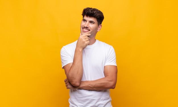Junger hübscher mann, der mit einem glücklichen, selbstbewussten ausdruck mit der hand am kinn lächelt, sich wundert und zur seite schaut