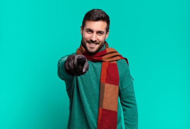 Junger hübscher mann, der mit einem zufriedenen, selbstbewussten, freundlichen lächeln auf kamera zeigt und sie wählt. kälte- und winterkonzept