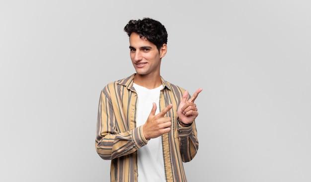 Junger hübscher mann, der mit einer positiven, erfolgreichen, glücklichen haltung lächelt, die auf die kamera zeigt und waffenzeichen mit händen macht