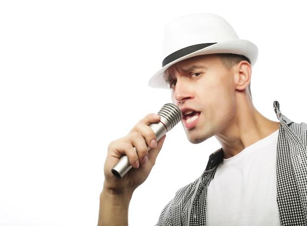 Junger hübscher mann, der mit mikrofon singt