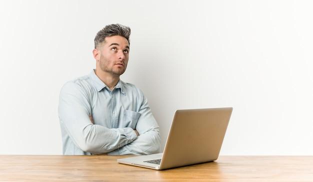 Junger hübscher mann, der mit seinem laptop arbeitet, der einer sich wiederholenden aufgabe müde ist.
