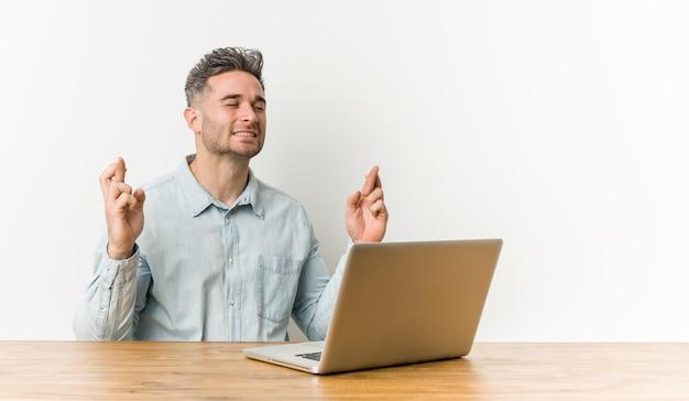 Junger hübscher mann, der mit seinem laptop arbeitet, der finger kreuzt, um glück zu haben