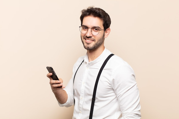 Junger hübscher mann, der mit verschränkten armen und einem glücklichen, selbstbewussten, zufriedenen ausdruck, seitenansicht nach vorne lächelt
