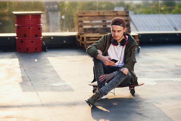 Junger hübscher mann, der musik in den kopfhörern und im telefon beim sitzen auf skateboard auf dem dach des industriegebäudes am sonnenuntergang hört.