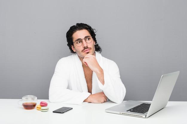 Junger hübscher mann, der nach einer dusche arbeitet, die mit zweifelhaftem und skeptischem ausdruck seitwärts schaut.