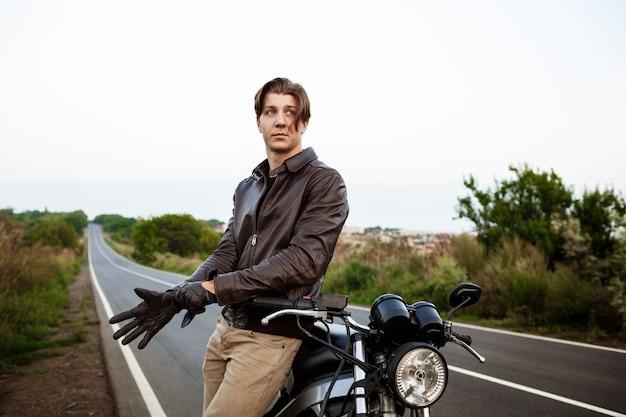 Junger hübscher mann, der nahe seinem motorrad aufwirft, handschuhe tragend.