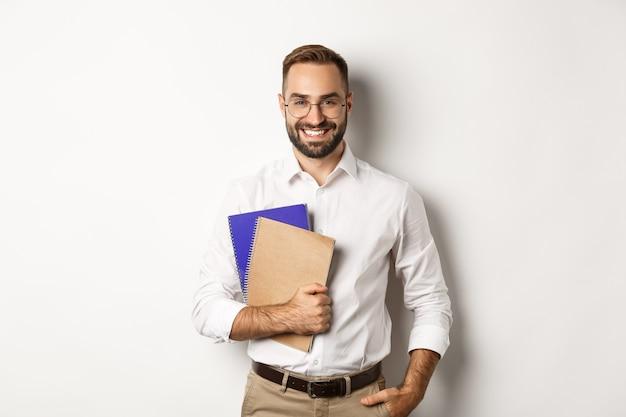 Junger hübscher mann, der notizbücher, konzept des e-lernens und kurse hält.