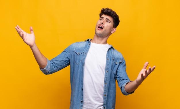Junger hübscher mann, der oper durchführt oder bei einem konzert oder einer show singt und sich romantisch, künstlerisch und leidenschaftlich fühlt