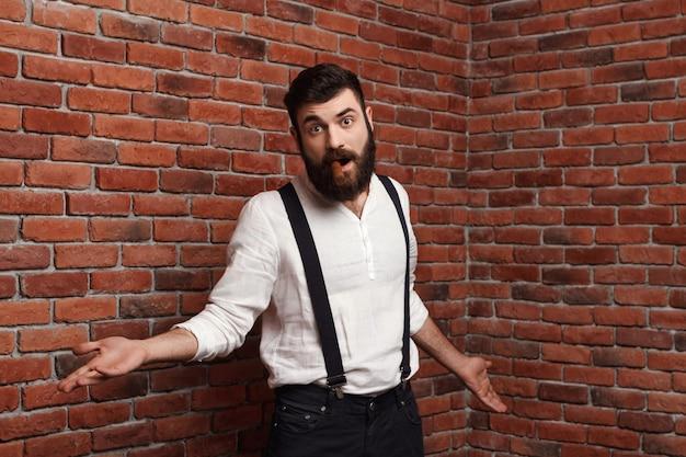 Junger hübscher mann, der rauchende zigarre auf ziegelmauer gestikuliert.