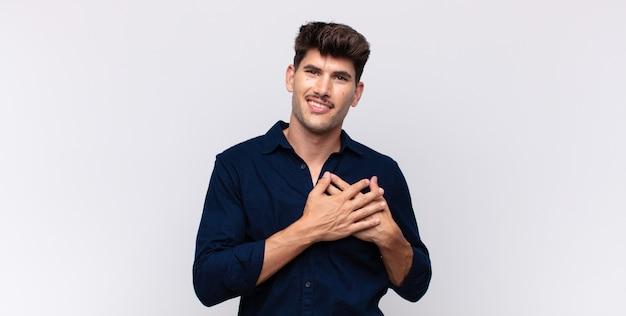 Junger hübscher mann, der romantisch fühlt, fröhlich lächelt und hände nah am herzen hält