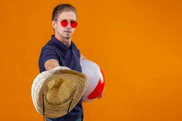 Junger hübscher mann, der rote sonnenbrille hält, die aufblasbaren ball hält und strohhüte mit dem sicheren ausdruck ausdehnt, der über orange hintergrund steht