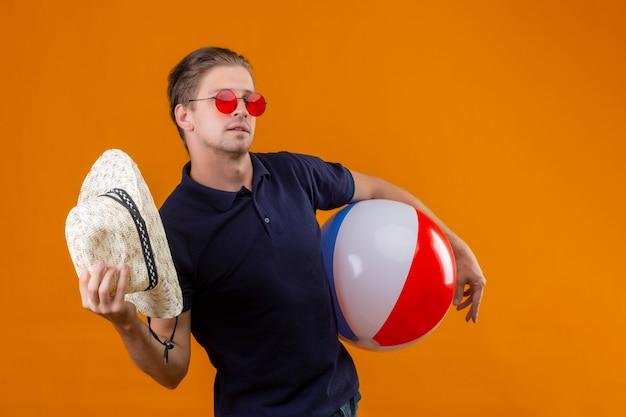 Junger hübscher mann, der rote sonnenbrille trägt, die mit aufblasbarem ball steht, der mit strohhut winkt, der über orange hintergrund zuversichtlich schaut