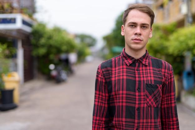 Junger hübscher mann, der rotes kariertes hemd in der straße trägt