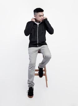 Junger hübscher mann, der schwarzen kapuzenpullover des kapuzenpullis trägt, sitzt in einem stuhl, während lokalisiert auf hintergrund geeignet für modell posiert