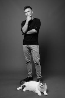Junger hübscher mann, der schwarzes hemd gegen graue wand trägt. schwarz und weiß