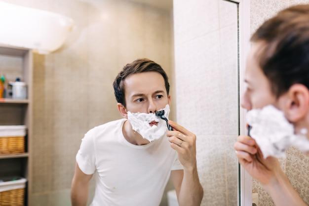 Junger hübscher mann, der sich am frühen morgen zu hause rasiert