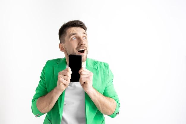 Junger hübscher mann, der smartphonebildschirm auf grauem hintergrund aisoliert zeigt. menschliche emotionen, gesichtsausdruck, werbekonzept.