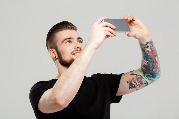 Junger hübscher mann, der telefon über graue wand betrachtet.