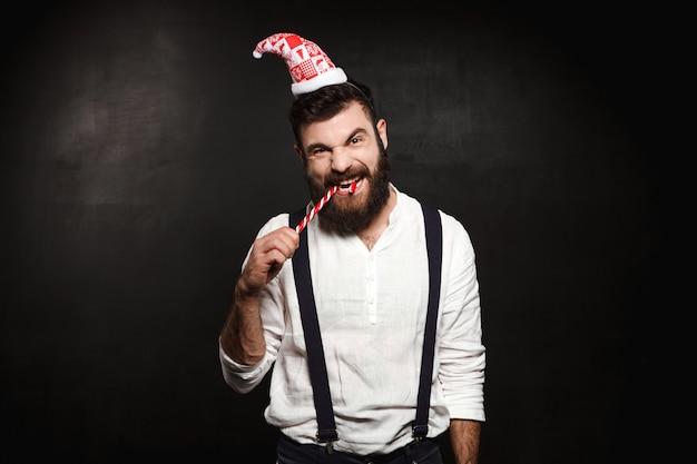 Junger hübscher mann, der weihnachtsbonbon über schwarz isst.