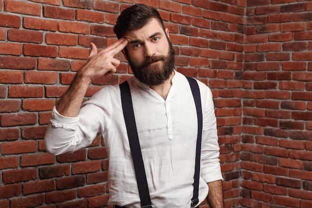 Junger hübscher mann, der zeigende finger am kopf auf ziegelmauer aufwirft.