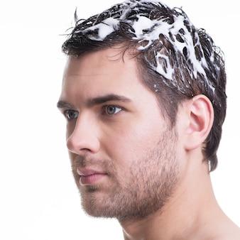 Junger hübscher mann des nahaufnahmeporträts, der haare mit shampoo wäscht - lokalisiert auf weiß.