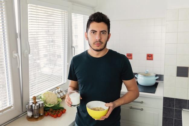 Junger hübscher mann frühstückt in der küche zu hause. der typ bereitete sich haferflocken und ein glas milch zum frühstück zu.