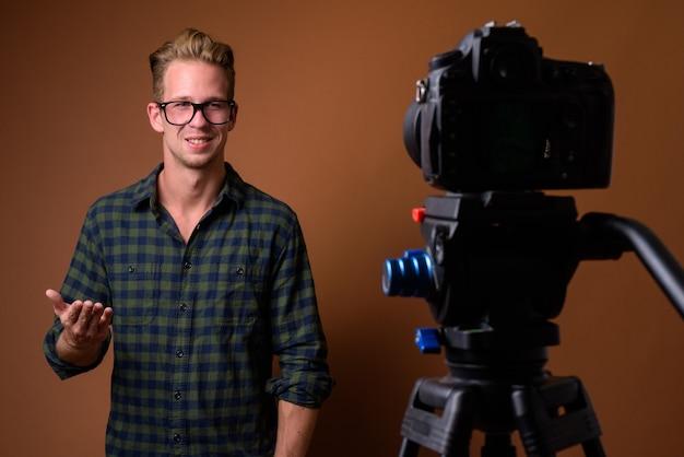Junger hübscher mann gegen braune oberfläche mit kamera