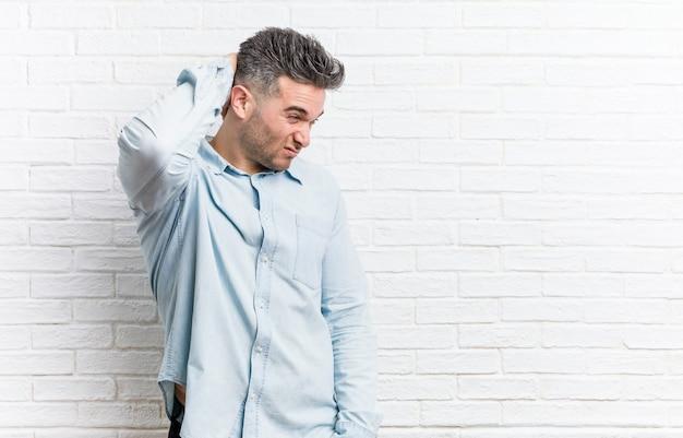 Junger hübscher mann gegen eine backsteinmauer, die hinterkopf berührt, denkt und eine wahl trifft.